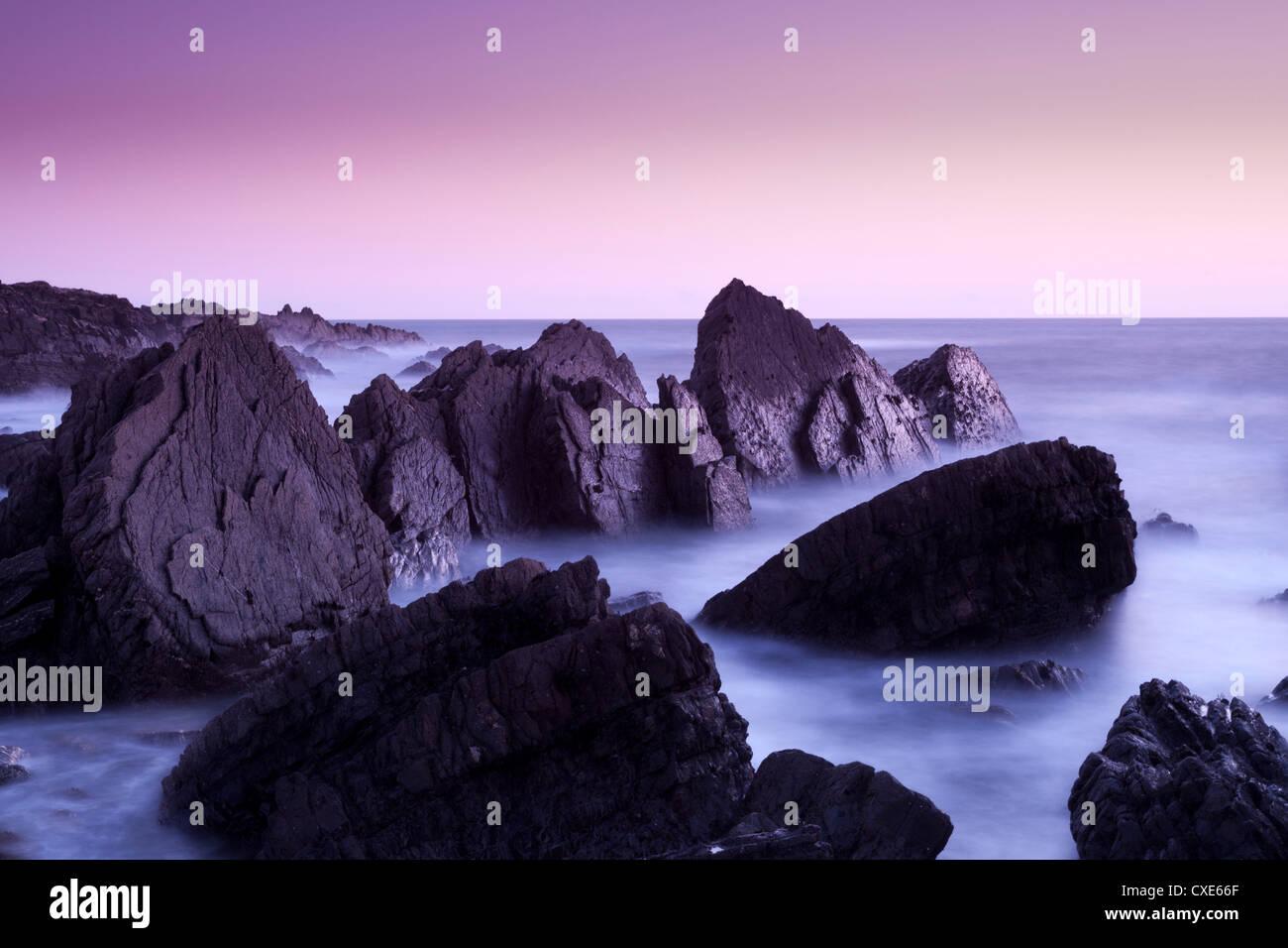 Waves moving over jagged rocks at Hartland Quay, Cornwall, England, United Kingdom, Europe - Stock Image