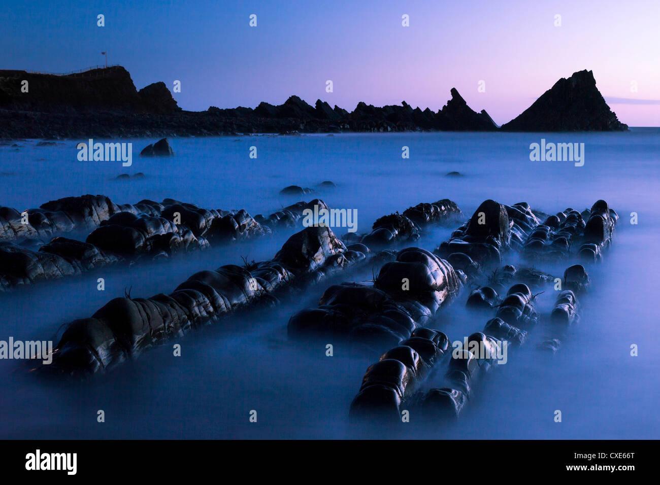 Waves moving over jagged rocks at dusk, on Hartland Quay beach, Cornwall, England, United Kingdom, Europe - Stock Image
