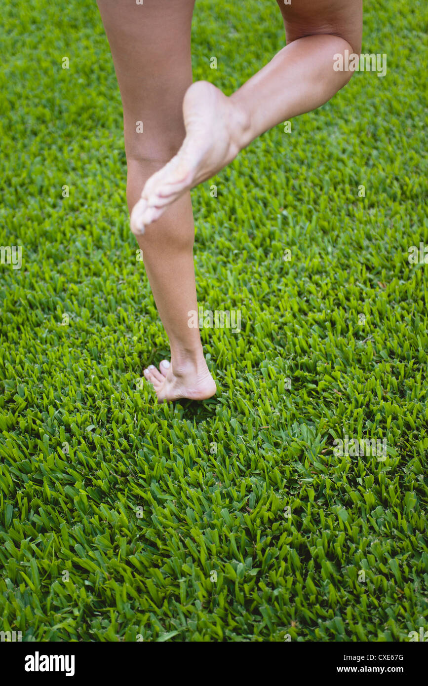 Barefoot woman standing on one leg in grass, low section - Stock Image