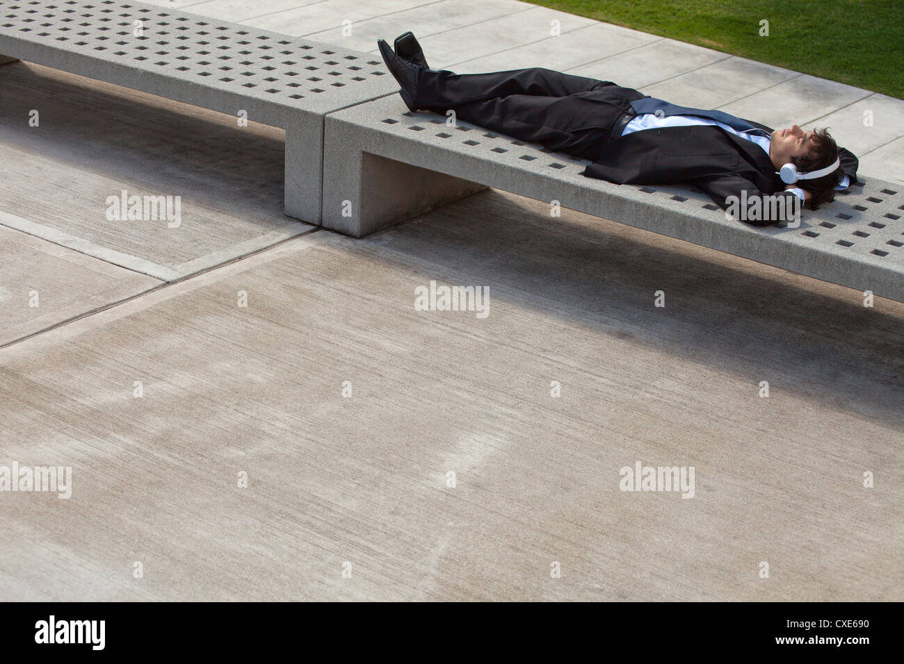 Young businessman napping on park bench with headphones on - Stock Image
