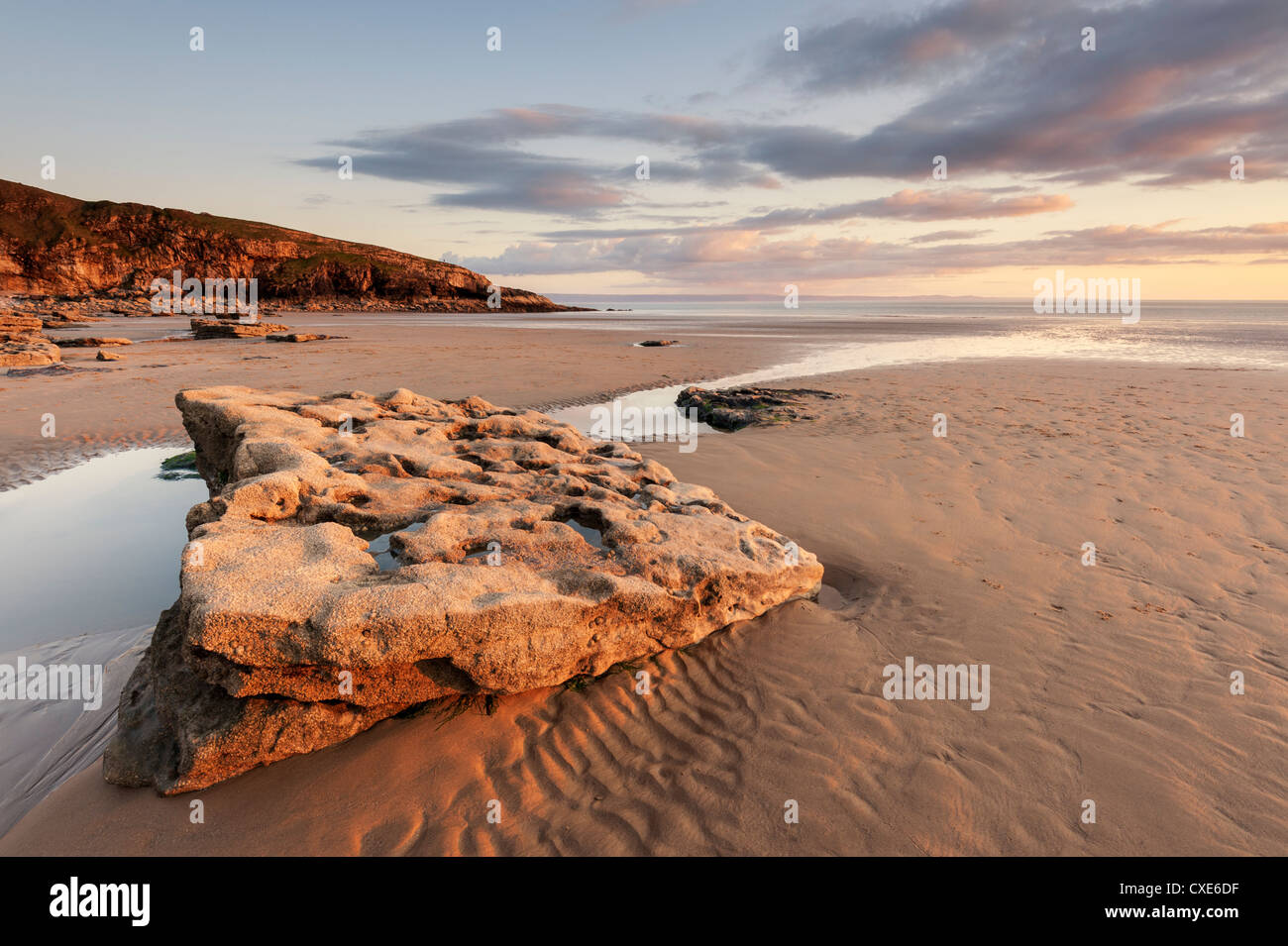 Sunset over rocks with flowing water at Dunraven Bay, Southerndown, Wales Stock Photo
