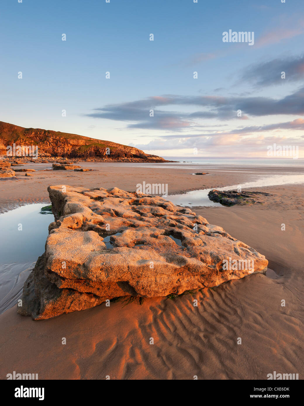 Sunset over rocks with flowing water at Dunraven Bay, Southerndown, Wales - Stock Image