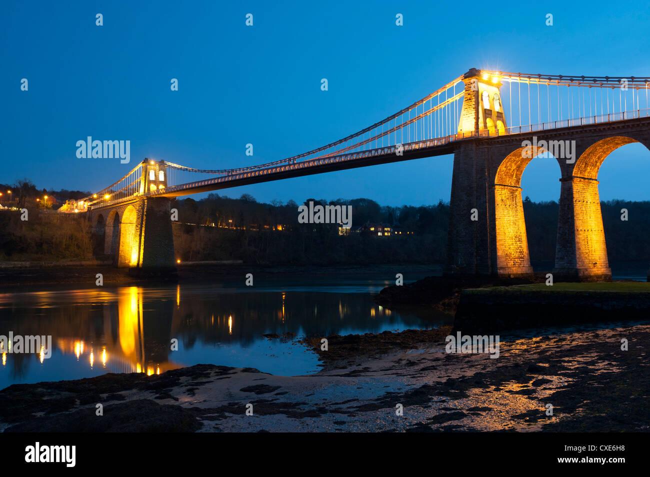Menai Bridge illuminated at dusk, Gwynedd, Anglesey, North Wales, Wales, United Kingdom, Europe - Stock Image
