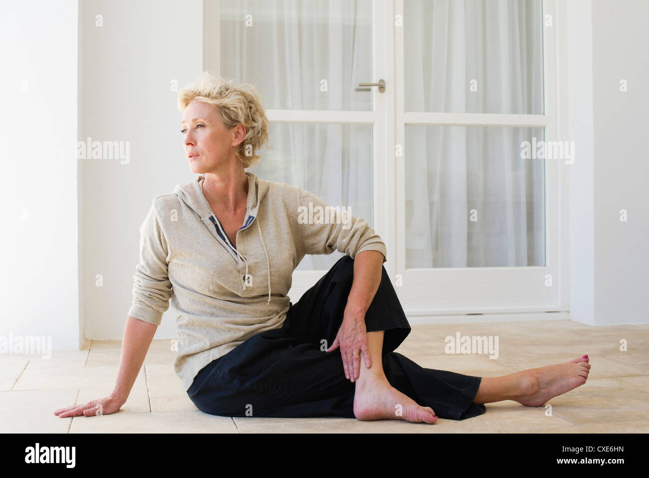 Mature woman sitting on floor doing spinal twist - Stock Image