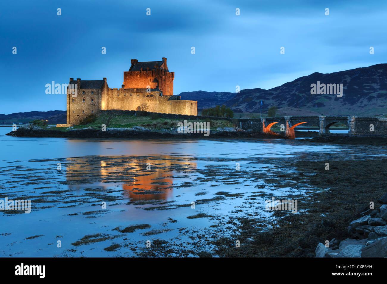 Eilean Donan (Eilean Donnan) Castle illuminated at dusk, Dornie, Loch Duich, Highlands Region, Scotland - Stock Image