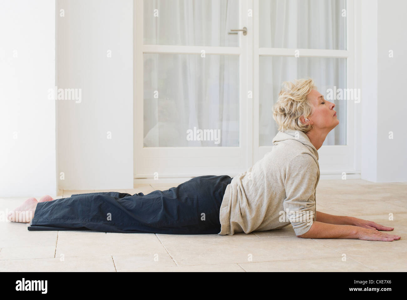 Mature woman doing cobra pose with eyes closed Stock Photo