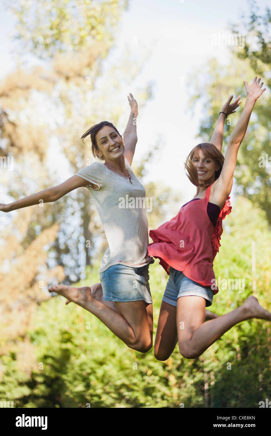 Young women jumping in air, smiling - Stock Image