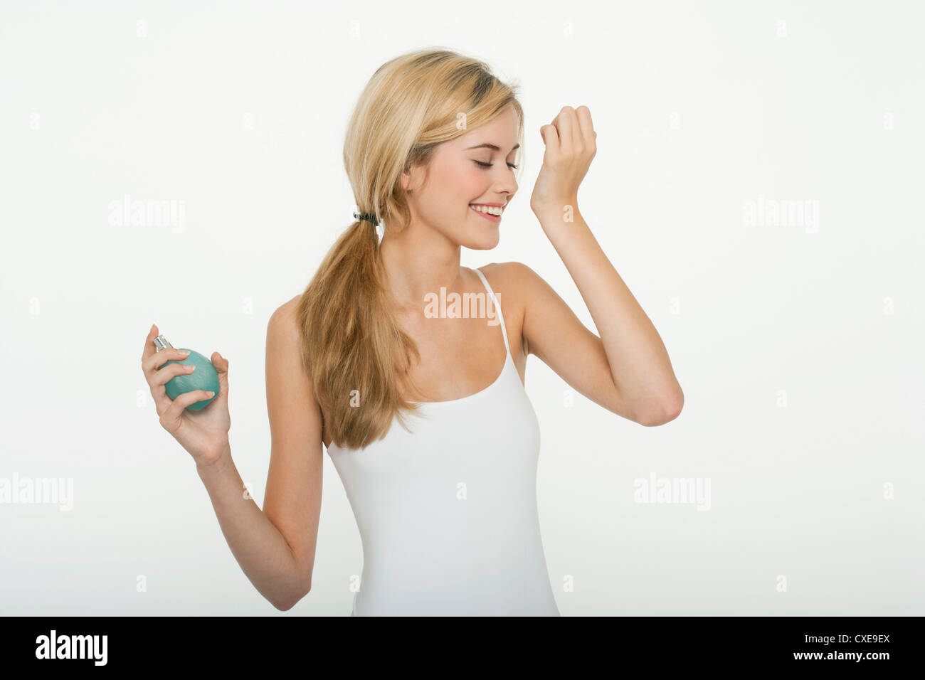 Teen girl smelling perfume - Stock Image