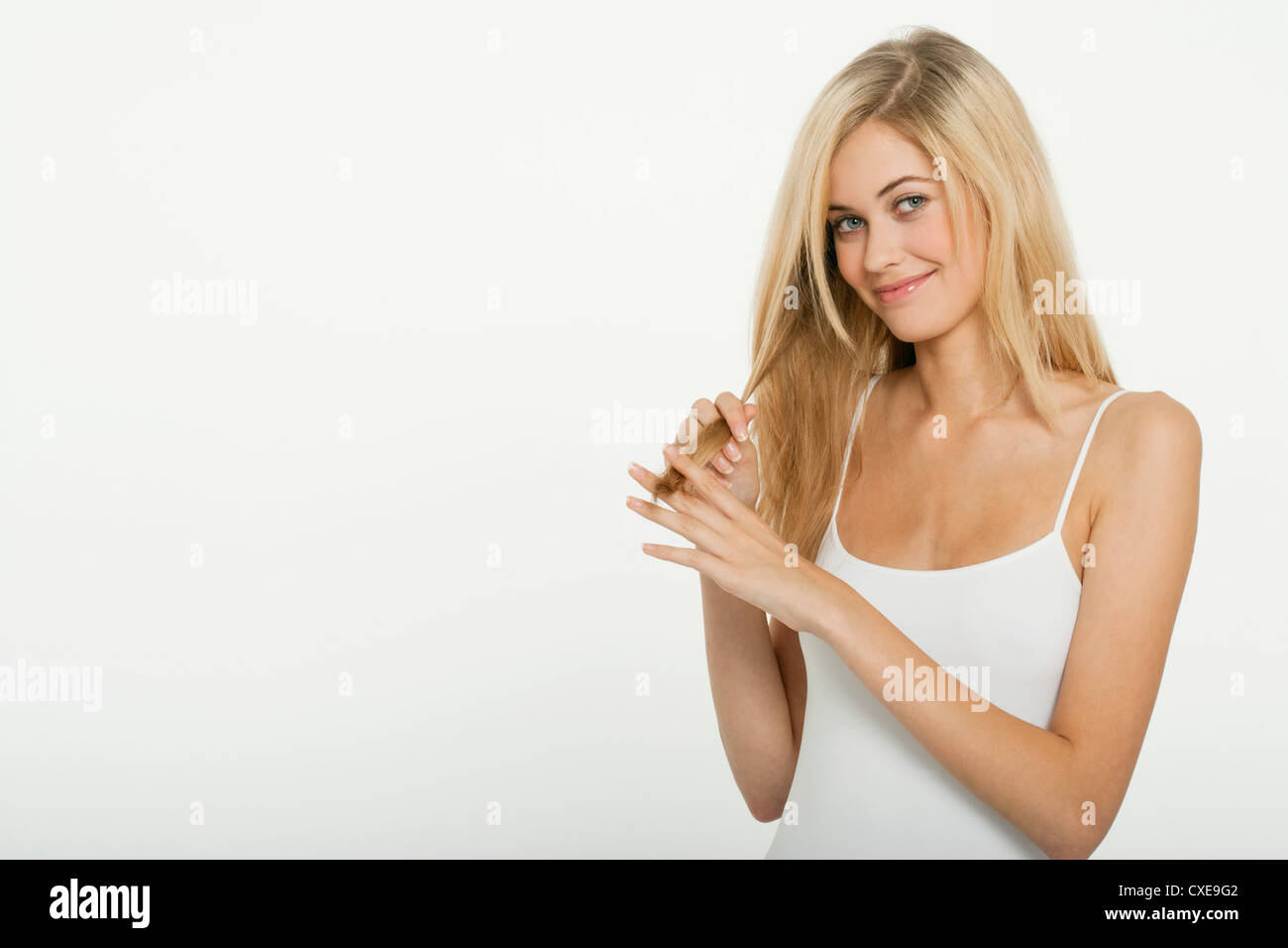Teen girl running her fingers through the ends of her hair - Stock Image