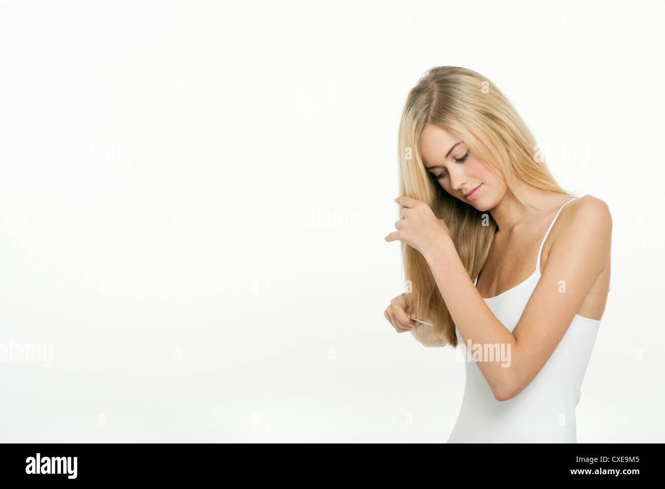 Teen girl combing her hair - Stock Image