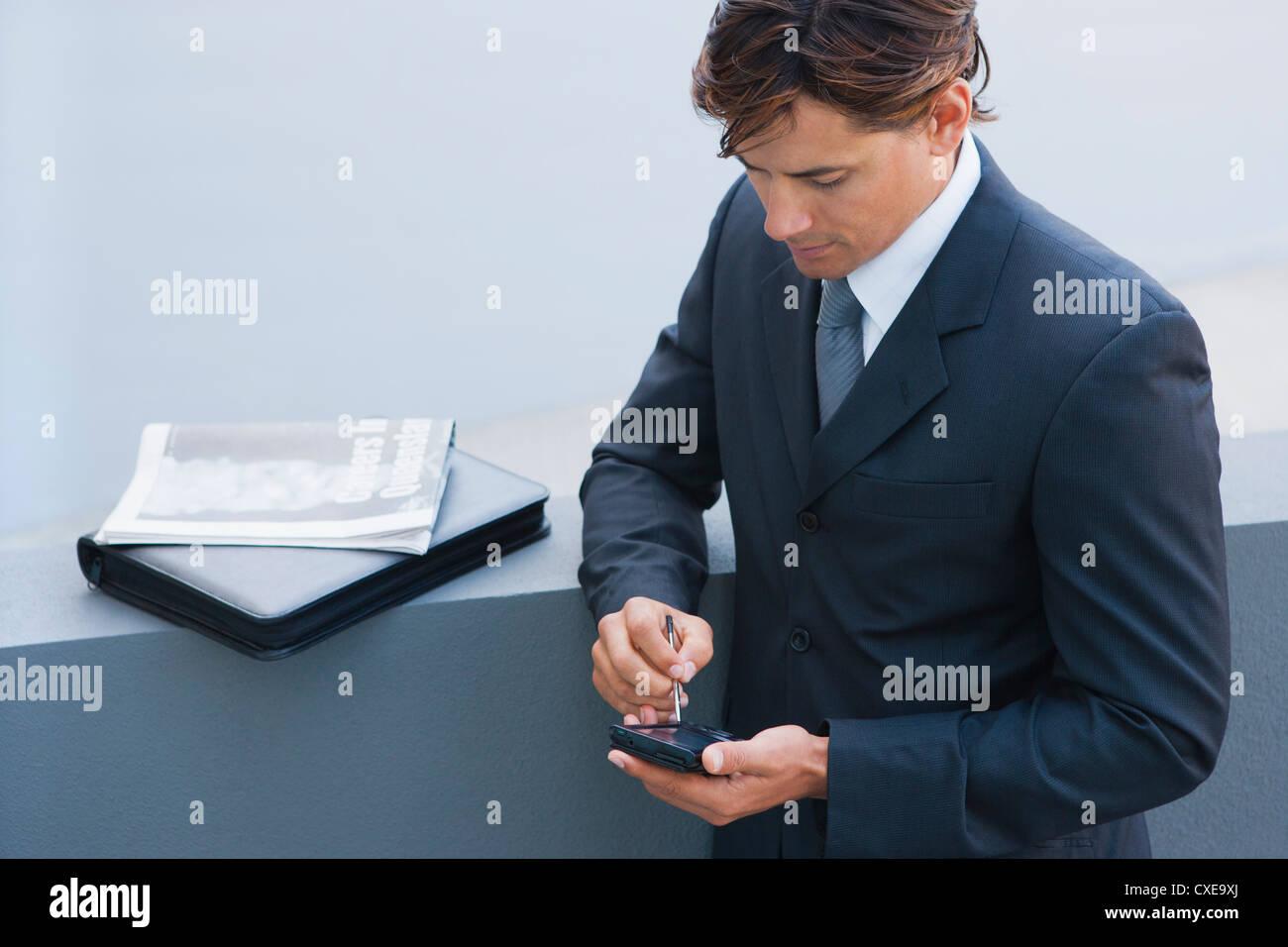Businessman using PDA - Stock Image