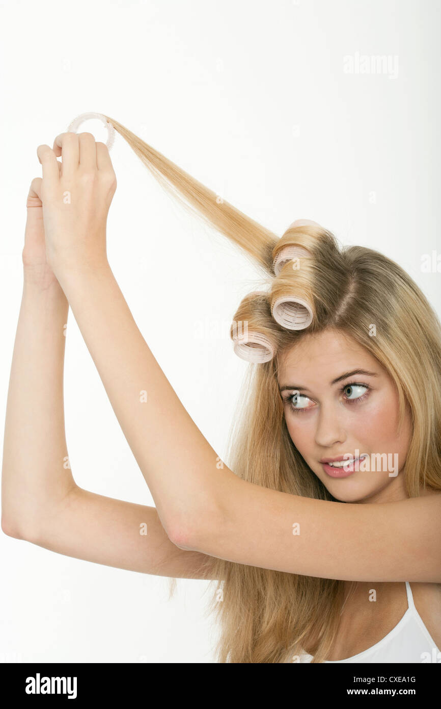 Teen girl rolling her hair with curlers - Stock Image
