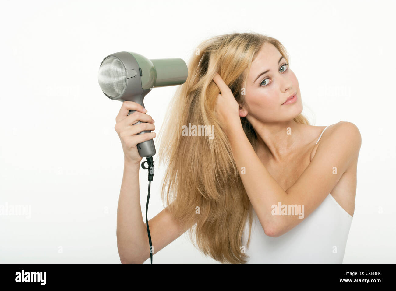 Teen girl using hairdryer - Stock Image