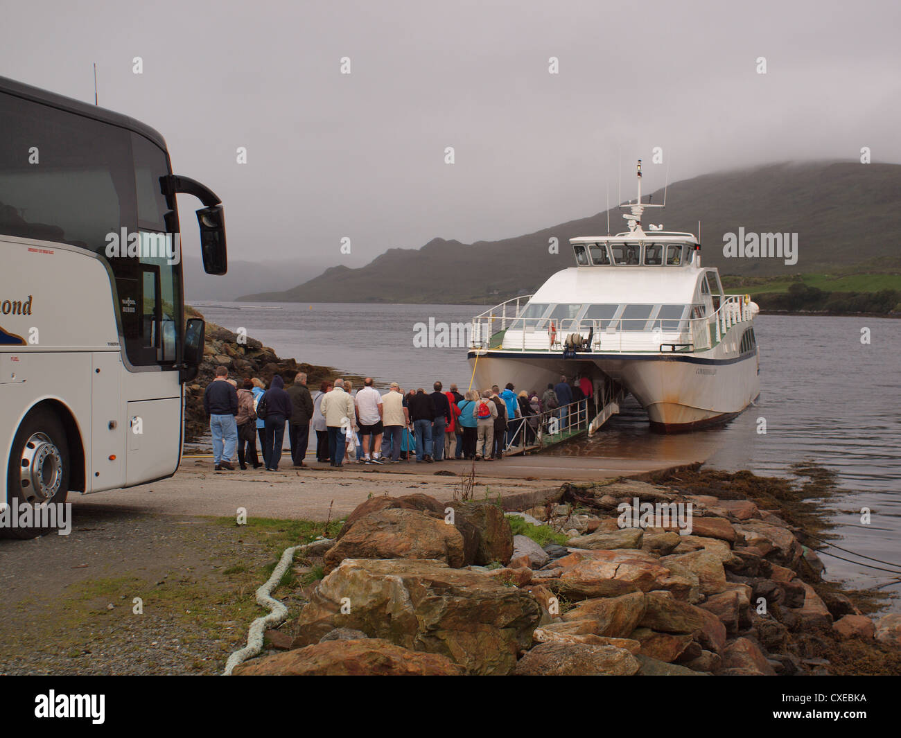 The Catamaran, Connemara-Lady preparing to embark passengers for a cruise along Killary glacial fjord in the West - Stock Image