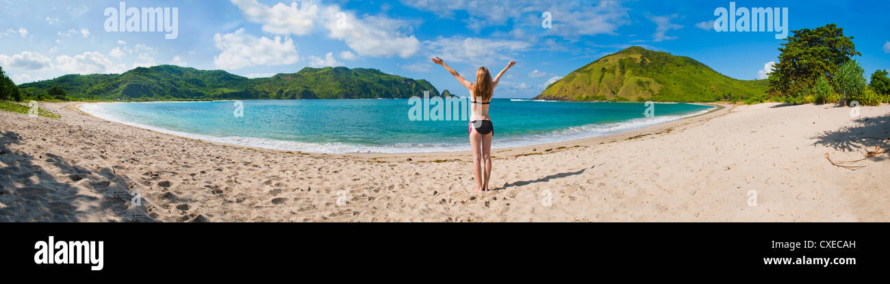 Woman enjoying freedom at Mawun Beach, a tropical paradise in South Lombok, Indonesia, Southeast Asia, Asia - Stock Image