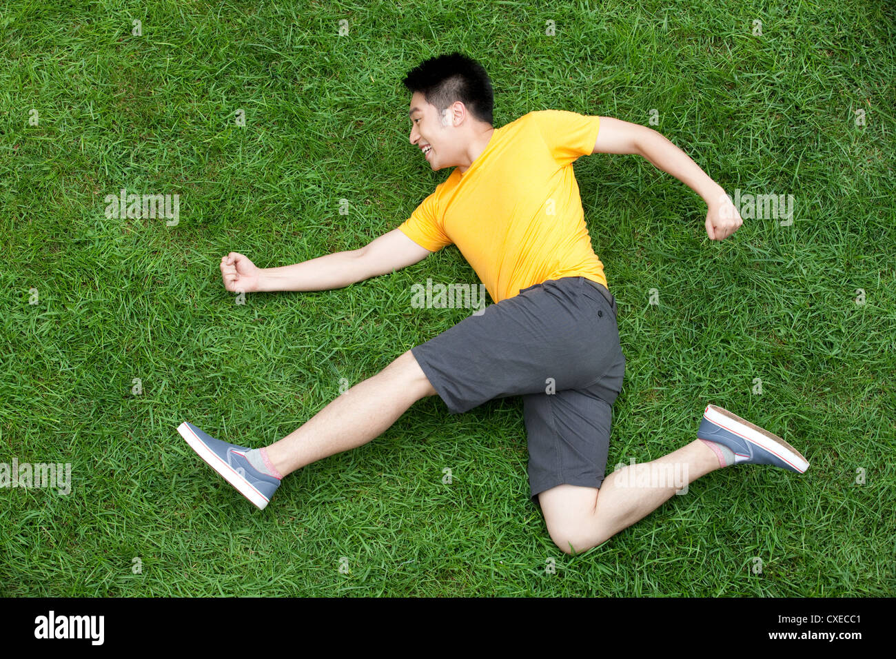 Creative young man imitating running on meadow - Stock Image