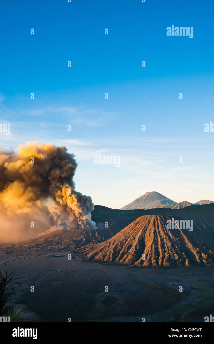Mount Bromo volcano erupting at sunrise, sending volcanic ash high into the sky, East Java, Indonesia, Southeast - Stock Image