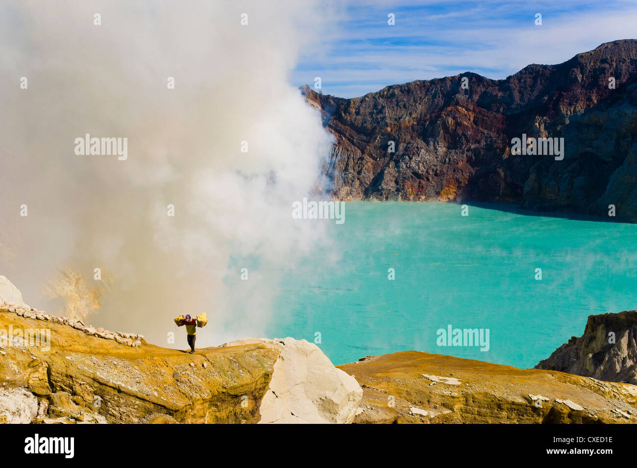 Sulphur worker appearing out of toxic fumes at Kawah Ijen, East Java, Indonesia, Southeast Asia, Asia - Stock Image