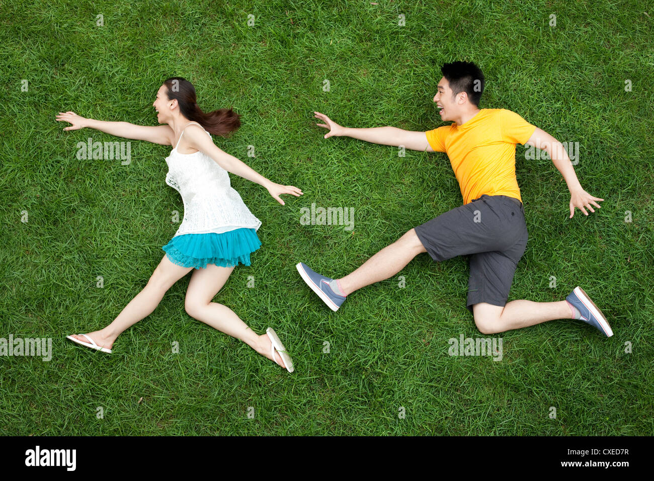 Young couple playing chase game on grass - Stock Image