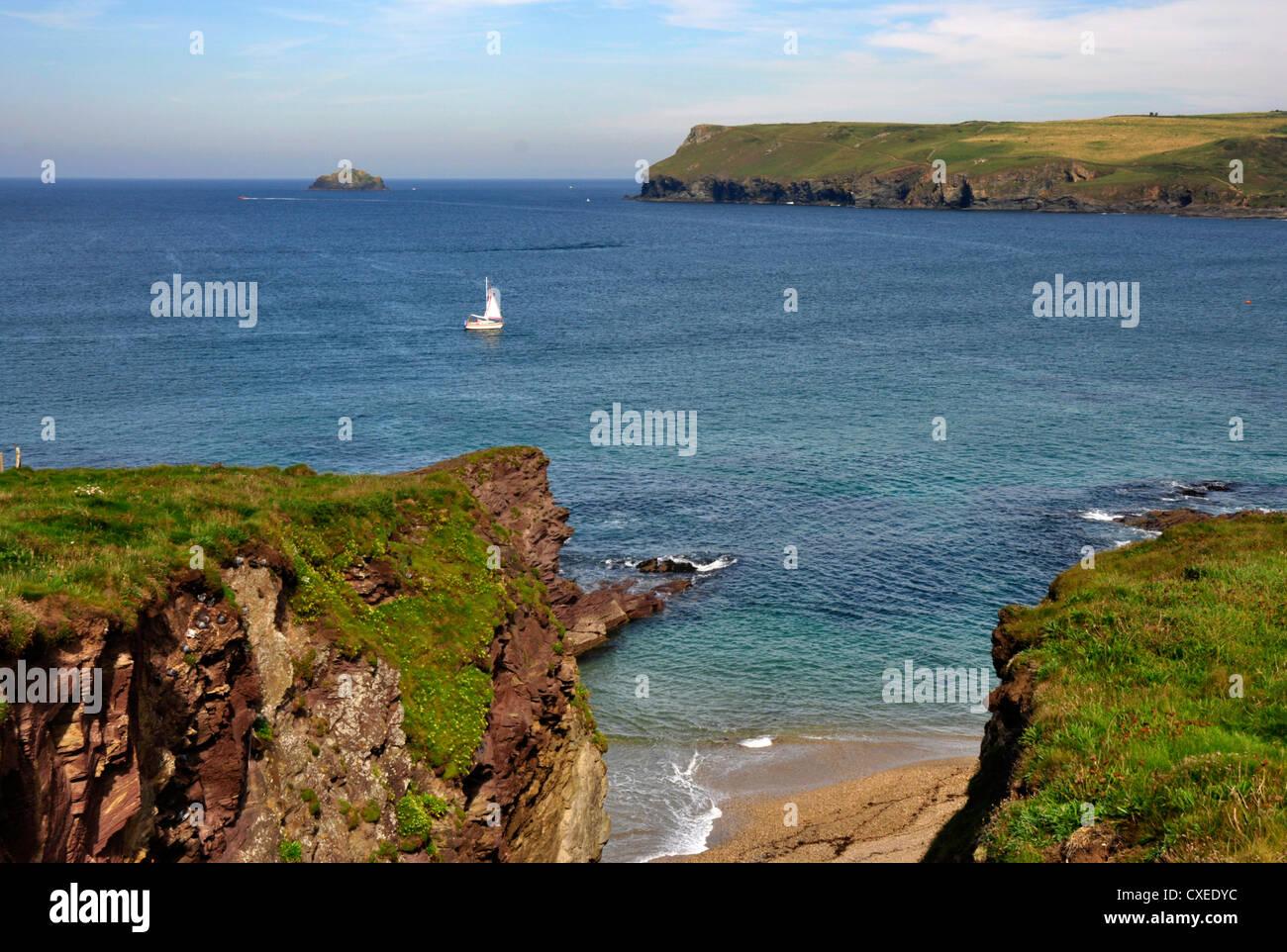 North Cornwall Coast path - near Polzeath - white sail  on azure blue sea - crossing Hayle Bay - backdrop Pentire - Stock Image