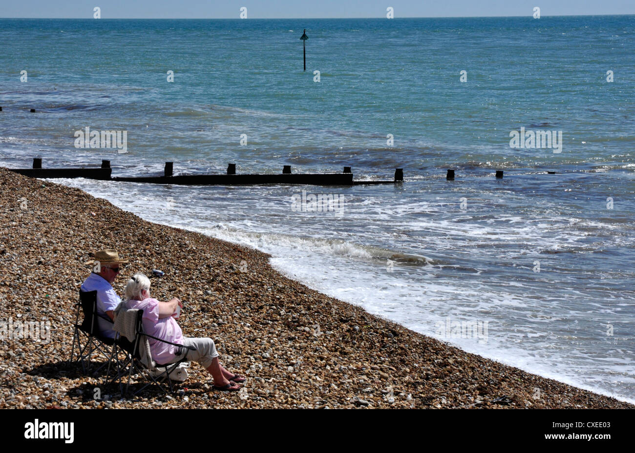 Elderly couple enjoying sea and sunshine - chairs on a pebble beach - gentle waves lapping the shore - Stock Image