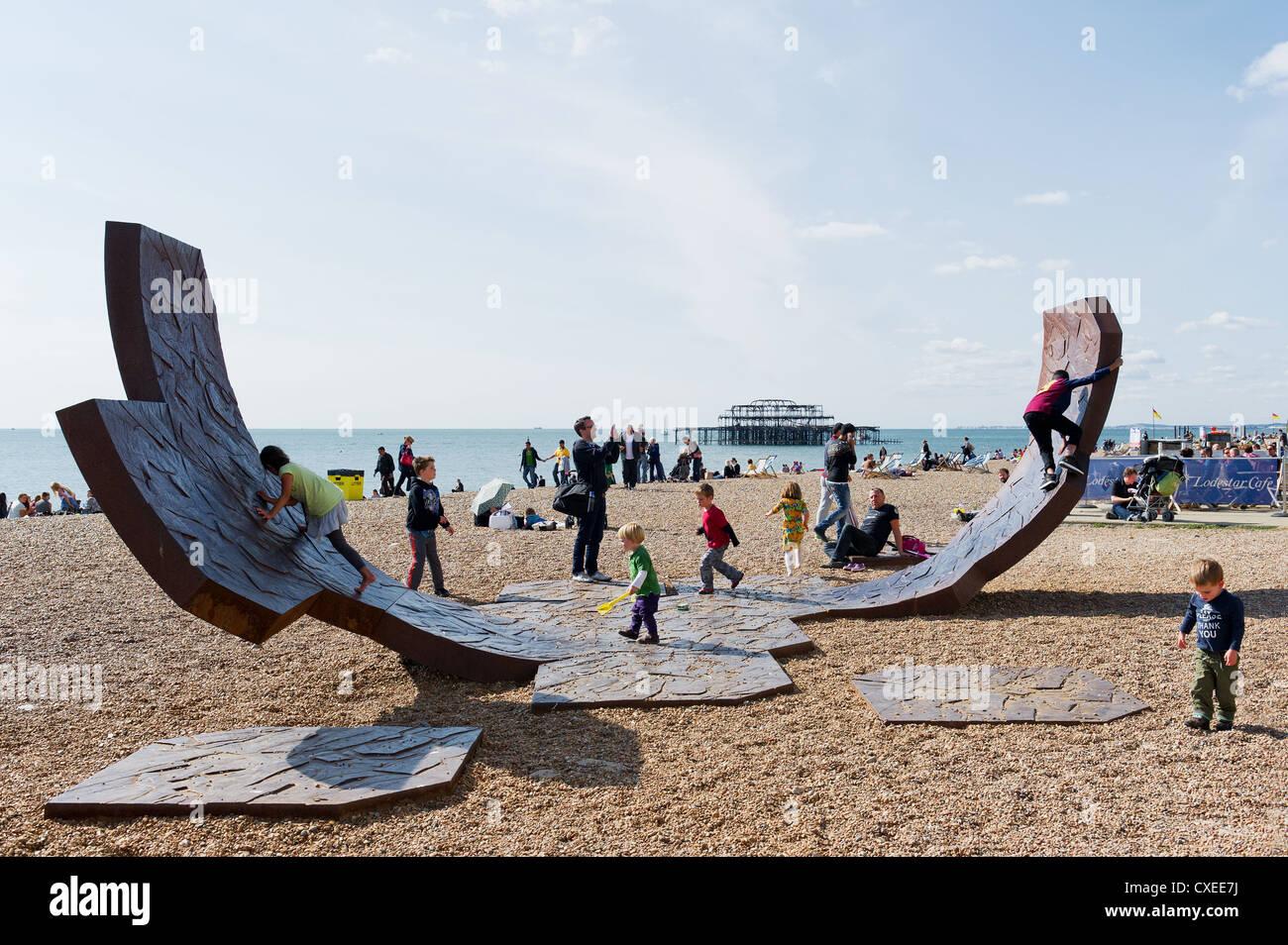 Children playing on the iron sculpture Passacaglia on Brighton beach Stock Photo