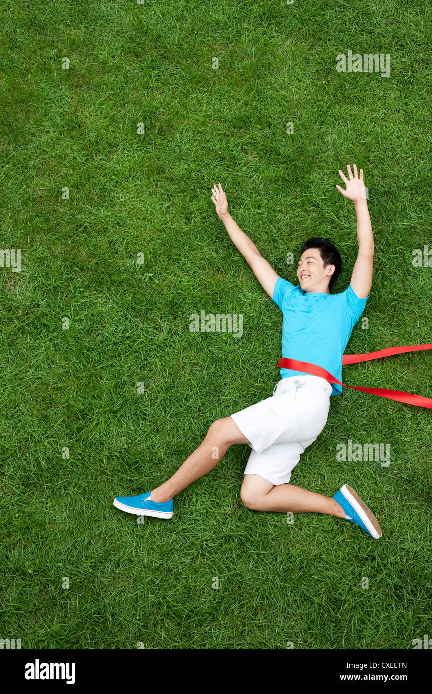 Creative young man imitating running attack on grass - Stock Image