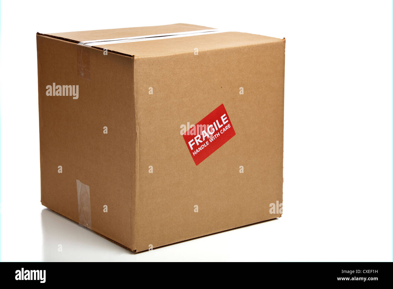 A blank, brown, corrugated cardboard box or shipping box with a 'Fragile - Handle with Care' sticker on - Stock Image