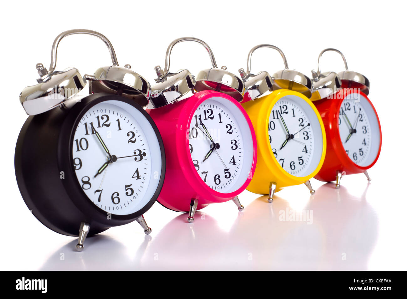 A row of colorful alarm clocks on a white background with copy space. Time concept - Stock Image