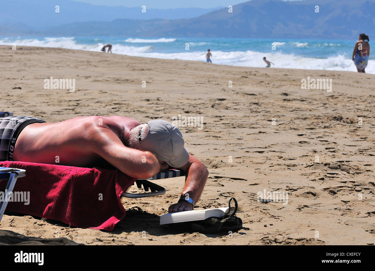 Sunbather reading a book from his lounger on Paralia  Kouma beach -West of Rethymnon ,  Crete Stock Photo