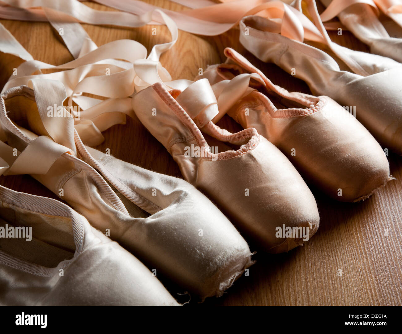 A group or background of used ballet pointe shoes or slippers on a wooden floor - Stock Image