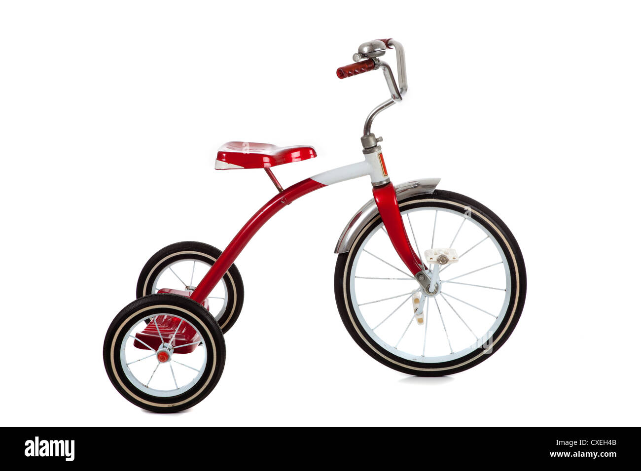 A child's vintage red tricycle on a white background - Stock Image