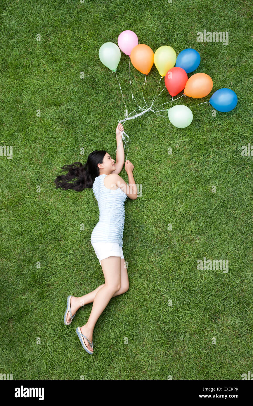 Young woman holding balloons on meadow - Stock Image