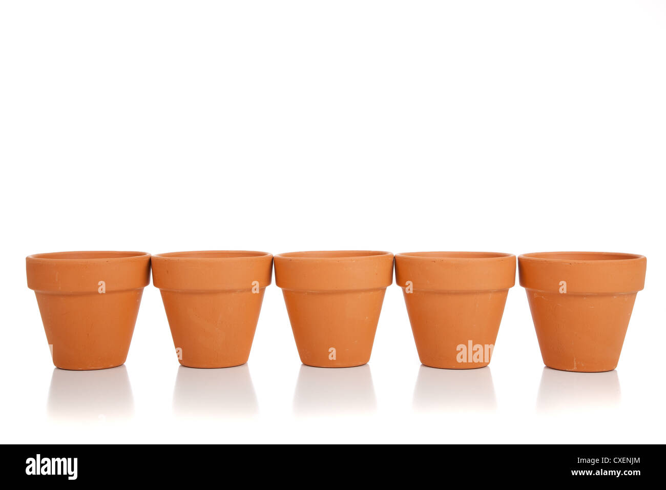 A row of orange clay pots on a white background - Stock Image