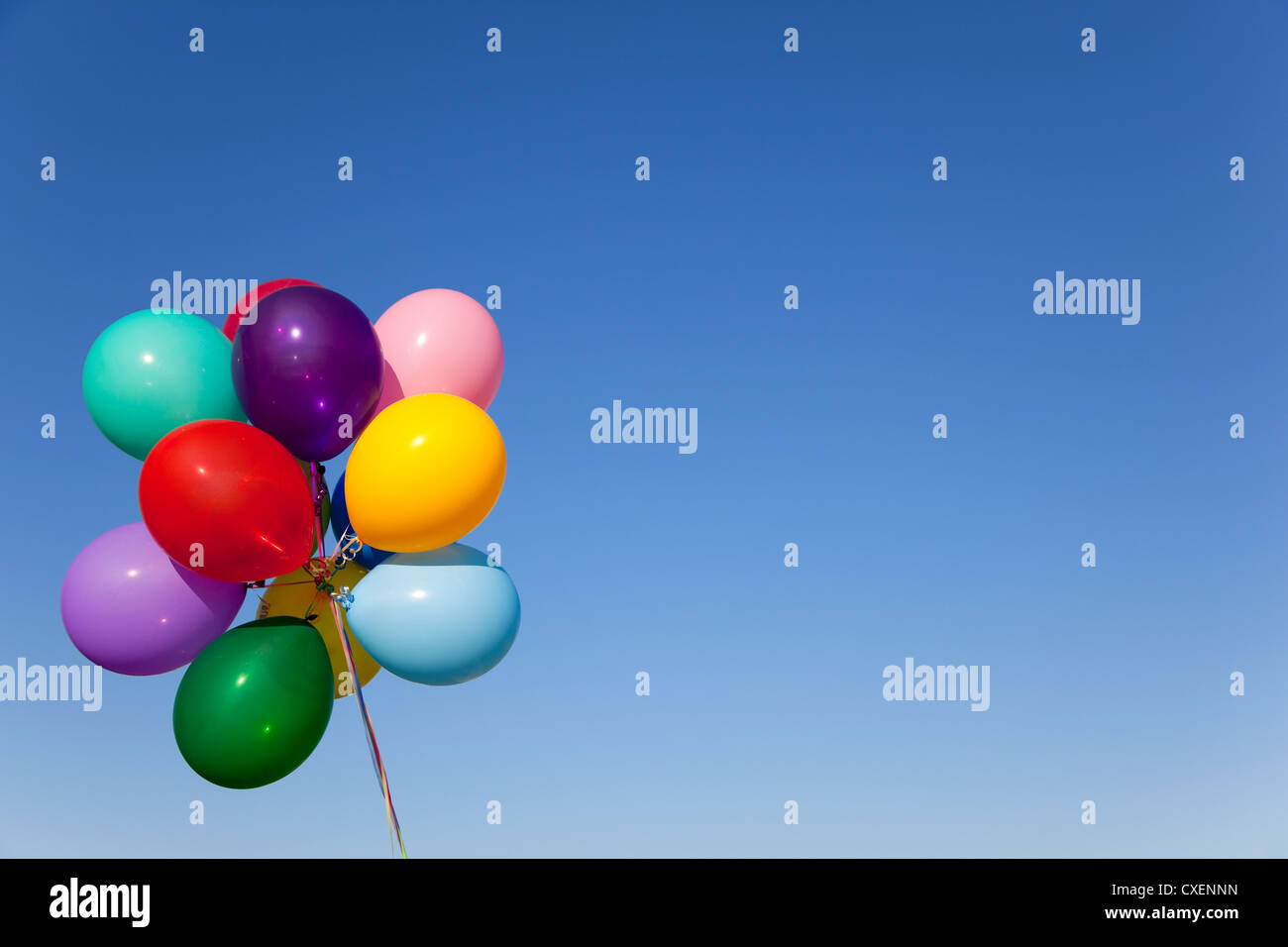 A brightly colored bouquet of balloons in front of a vivid blue sky with copy space - Stock Image