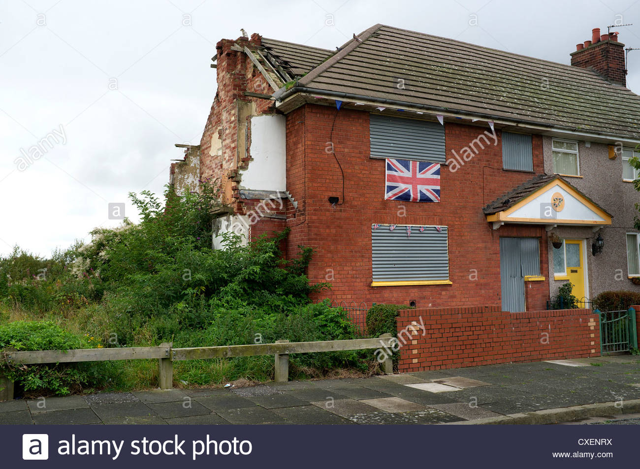 Derelict house next to an occupied home, no.8, in Ilchester Road in Birkenhead, Wirral, UK. - Stock Image
