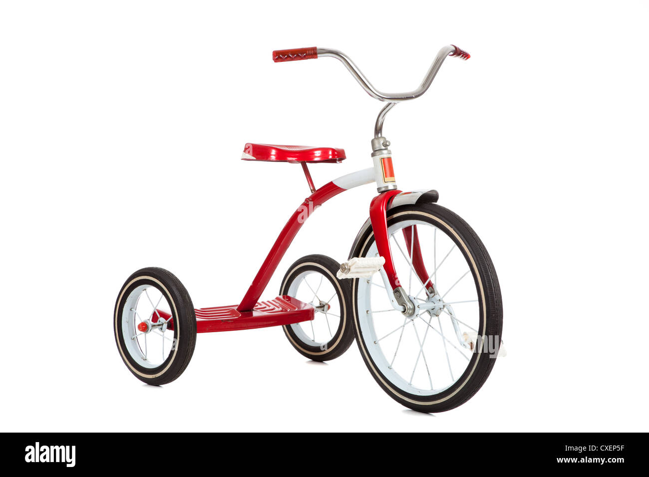Red vintage tricycle on a white background - Stock Image