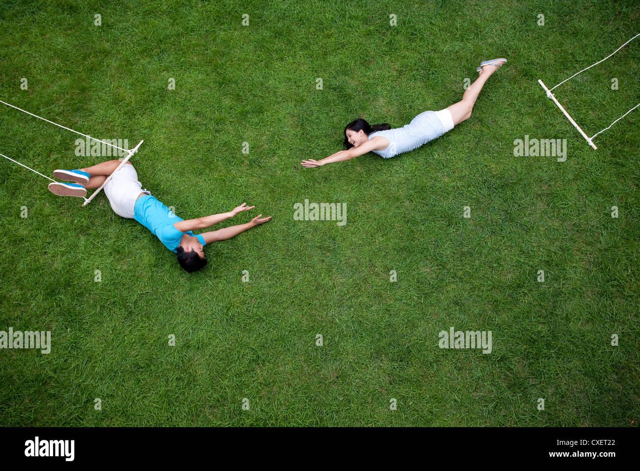 Creative young couple imitating aerialist - Stock Image