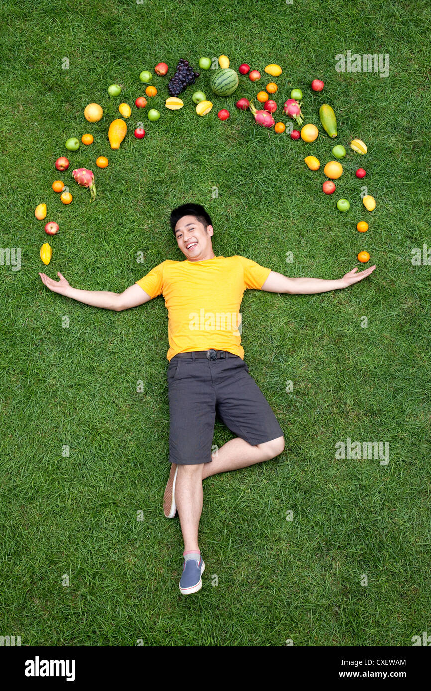 Young man with fresh fruits on meadow - Stock Image
