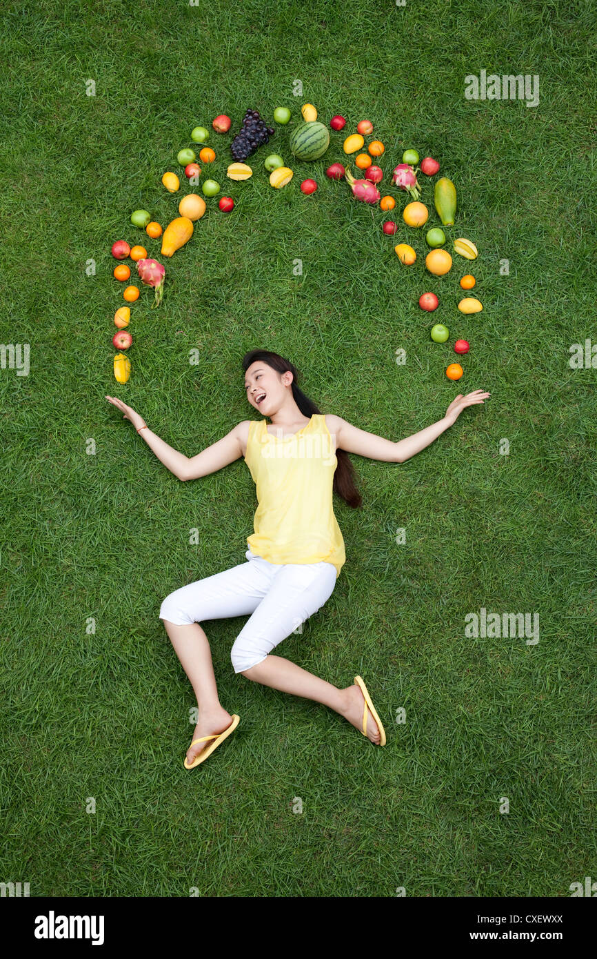Young woman with fresh fruits on meadow - Stock Image