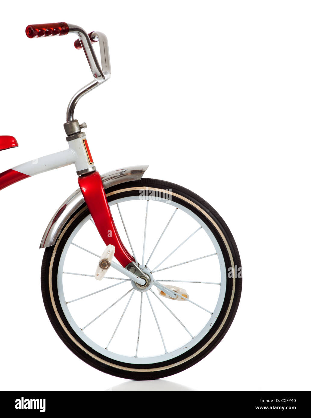 Front wheel of a red tricycle on a white background - Stock Image