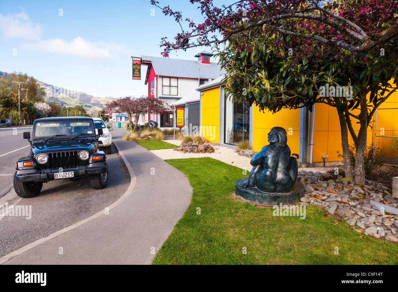The main street in the village of Little River, Canterbury, New Zealand, with New Zealand Art and a jeep parked - Stock Image