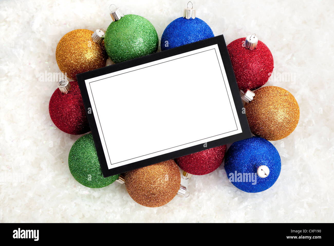 A Christmas themed note-card or message surrounded by baubles and ribbon. Use as invitation or announcement, with - Stock Image