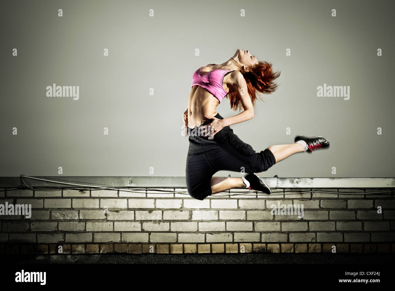 girl jumping on the roof - Stock Image