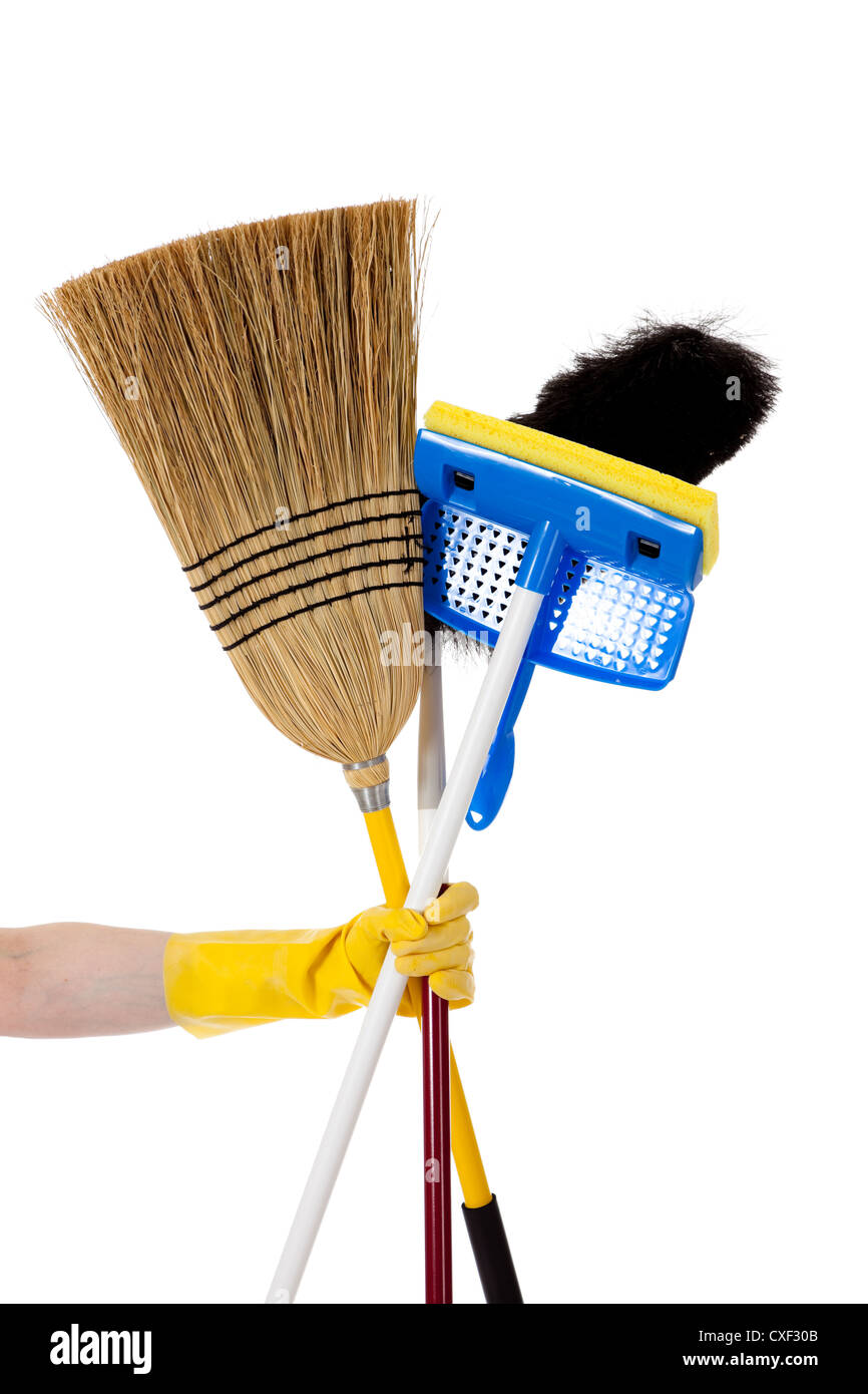 Rubber gloved hand holding a broom, mop and duster - Stock Image