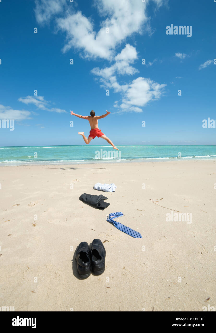businessman jumping on the beach Stock Photo