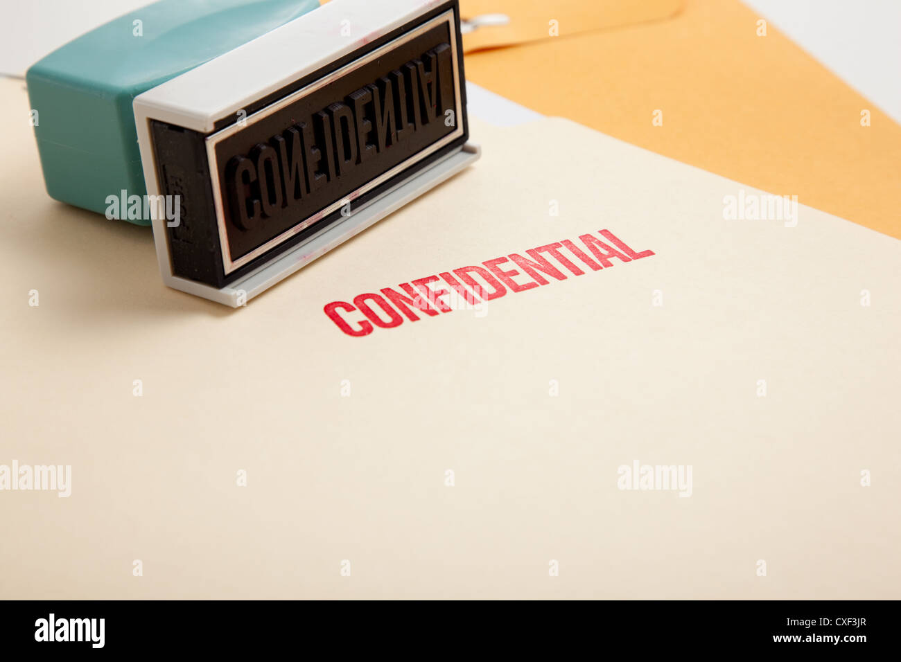 Confidential stamp on a file folder - Stock Image