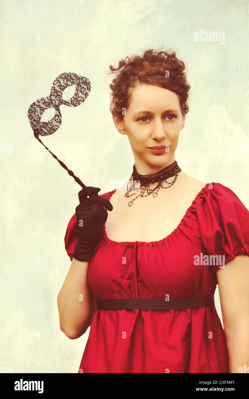 a woman in a red period dress and with a venetian mask - Stock Image