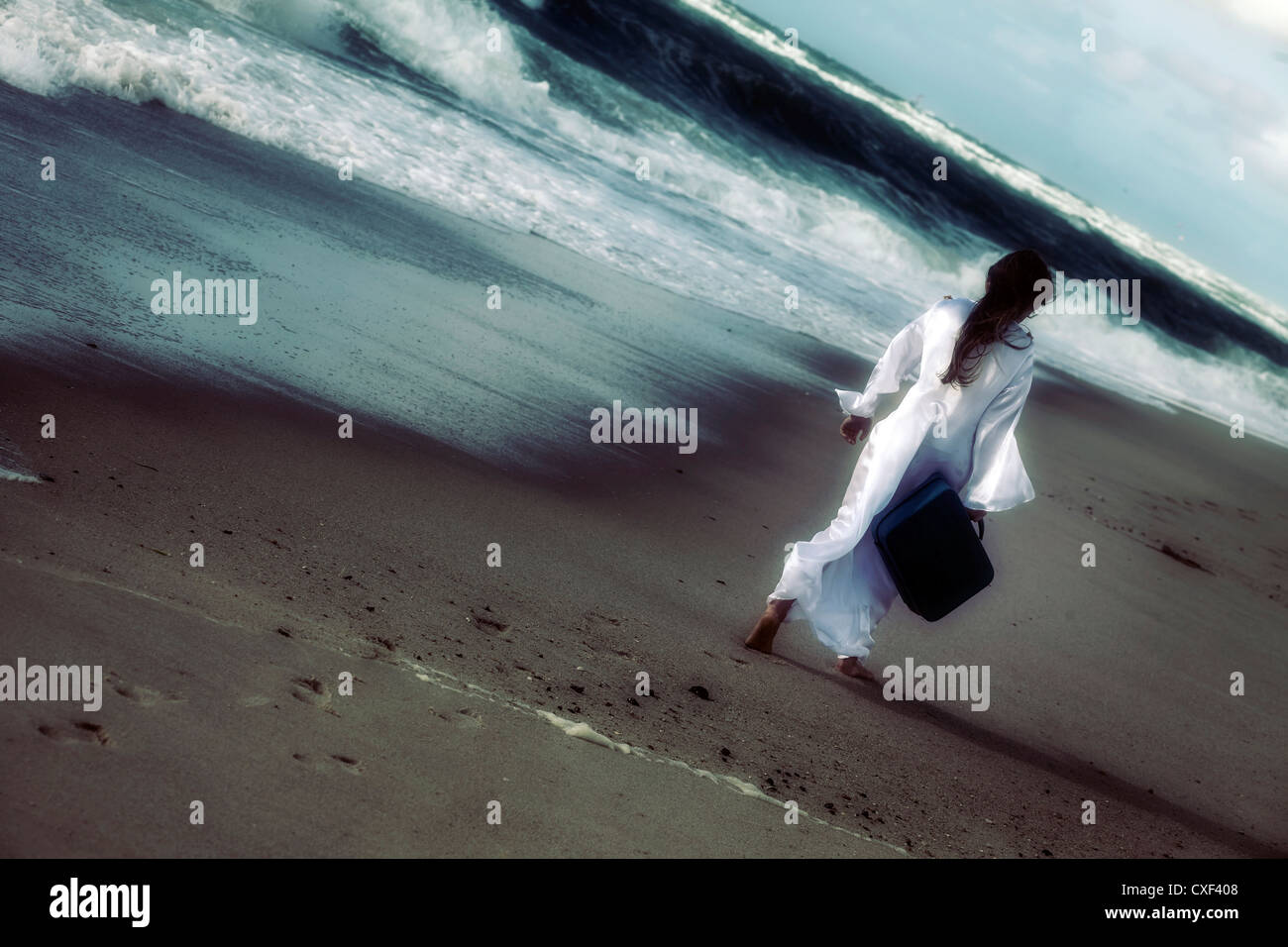 a girl in a white dress at the sea with a suitcase - Stock Image