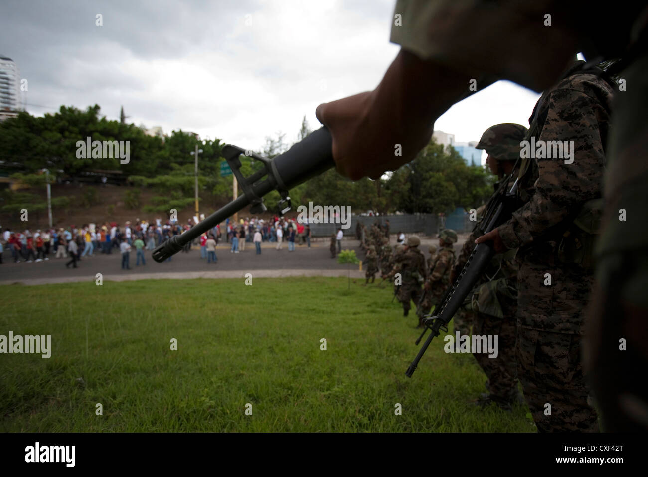 Honduran soldiers stand guard as supporters of Honduras' ousted President Manuel Zelaya pass by during a march Stock Photo